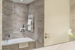 Foto di una vasca da bagno con bottiglia e calici in una Superior