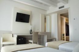 Foto di due letti singoli con la TV in una stanza Superior